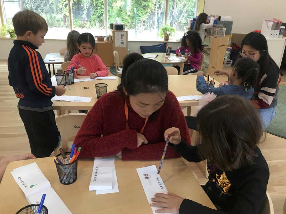 Teachers work with elementary school children on Chinese language skills.