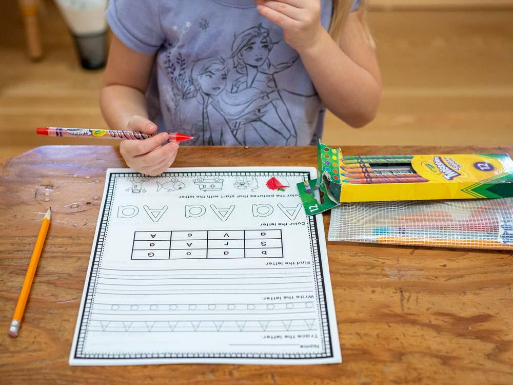 A kindergarten student studies English alphabet letters.