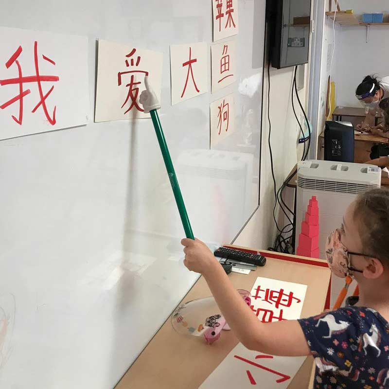 Young student pointing at Chinese character on a whiteboard.