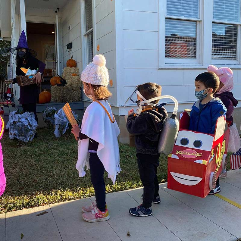 Young students trick or treating in Halloween costumes.