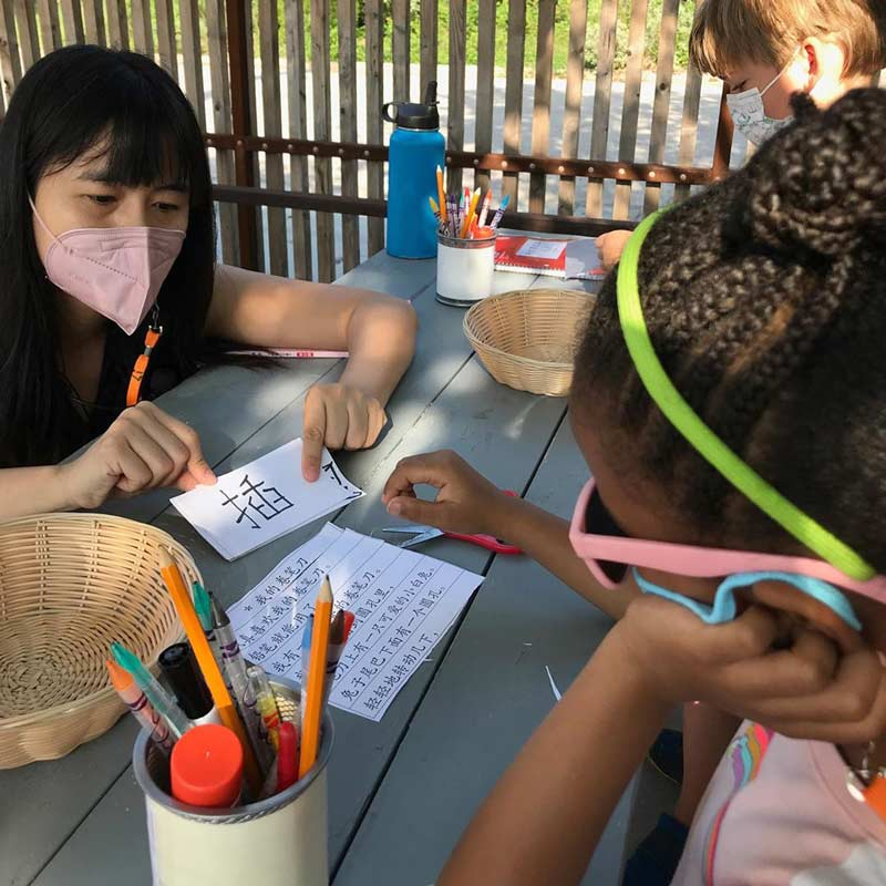 A student learning Chinese writing outside at a picnic table.